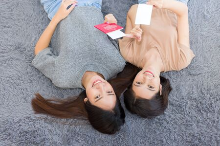 Two young Asian women lying on the floor and holding passports smiling happily. Pretty girls planning a vacation trip in the summer at home.