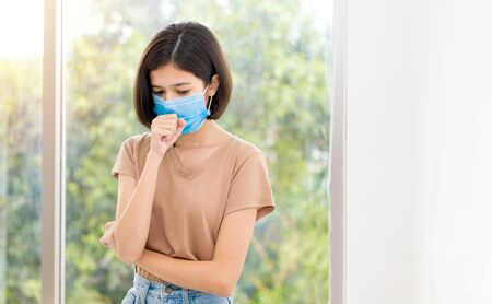 Asian young woman is wearing a face mask and coughing due to illness indoors.