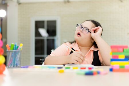 Autism girl practicing to write her own name. Training for intelligence restoration for children with autism or aphasia kids. Stock Photo