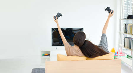 Two young Asian women holding game joysticks and competing happily while sitting on the sofa. Competitive friends playing video games at home. Stock fotó