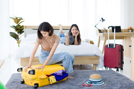 Young Asian woman preparation travel suitcase at home while her friend lying on the bed and were laughing at him Because of too many clothes. Imagens