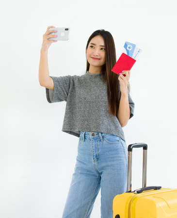 Asian young woman taking a selfie with a passport, airline ticket, and suitcase Before boarding time for a summer trip.