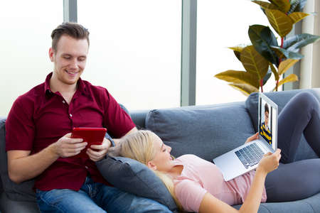 Young couples chatting video calls streaming online on a laptop, a Young woman lying on his boyfriend's lap on the sofa. Zdjęcie Seryjne