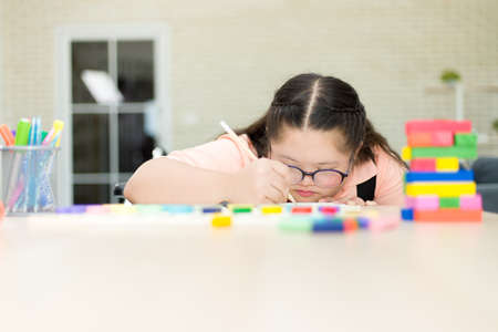 Autism girl practicing to write her own name. Training for intelligence restoration for children with autism or aphasia kids.