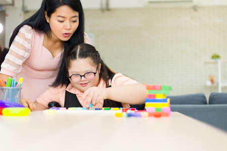 Autistic cute girl practicing connecting the color sticks at home while her mom kept watching nearby. Training for intelligence restoration for children with autism or aphasia kids.