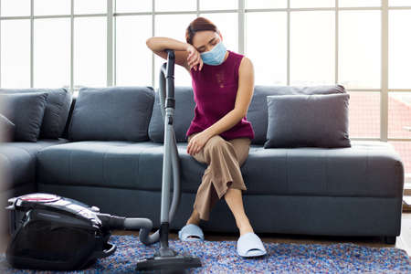 Asian housewife is sitting on the sofa with a vacuum cleaner. She is feeling tired from doing housework.