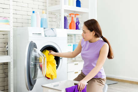 Asian housewife is separating clothes from the basket and put them into the washing machine for laundry. Young woman is happily doing housework.