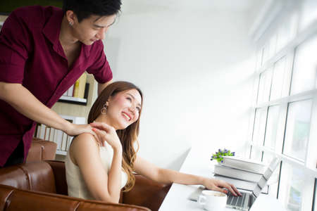 Asian young woman is using laptop work at home while the husband massaged her shoulder to relieve pain.