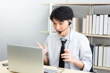Asian male teacher or tutor wearing a headset, He was teaching students via video conferencing system on a laptop from home. The young man is meeting with colleagues at the webinar. Stockfoto