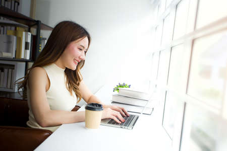 Attractive young woman is sitting working near the window while having sunshine in the morning, She using the laptop with a coffee cup put on the side.
