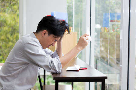Asian man is stressed because he has been fired from work. Dismissed employees Due to the economic downturn and to the epidemic COVID-19.