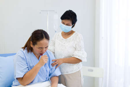 Female patient in a patient's outfit sits on a hospital bed was coughing while her mother stood and takes care nearby.