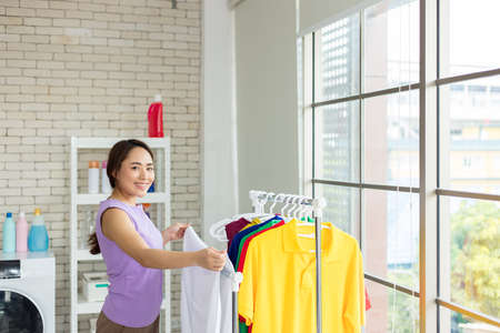 Housewife is drying clothes on the clothesline after laundry. Asian young woman is happily doing housework.