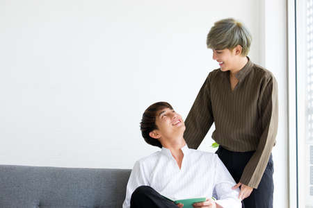 Happy Asian male or couples are sitting on the sofa bed, Both of them are making eye contact together in the mood of love and good relationship. Concept of LGBTQ pride.