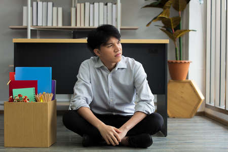 Asian man is stressed because he has been fired from work. Dismissed employees Due to the economic downturn and to the epidemic contagious disease. Stock Photo