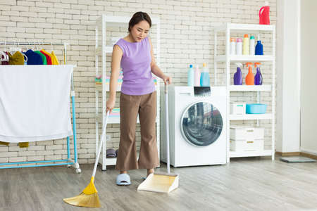 Asian young woman or maid is sweeping, cleaning dust on the floor at home. The housewife is doing housework happily during the weekend. Banco de Imagens