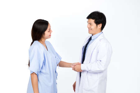 The doctor and the patient stand hand in hand as a thank you for the treatment. Isolated on white background.
