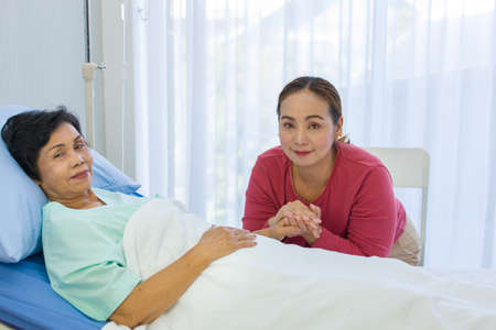 The lovely daughter comes to visit the sick mother while her mom is recuperating at the hospital. Elderly health care concept.