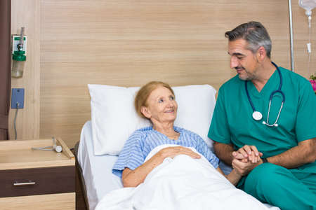 Doctor and elderly patient smile happily while in the recovery room within the hospital. Caring for the elderly concept. 免版税图像