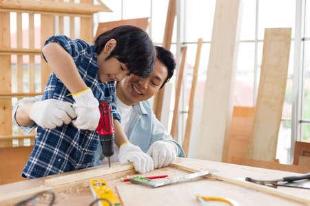 Asian father teaches his son to do carpentry at home. Reklamní fotografie