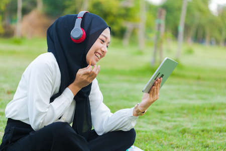 Young Muslim woman resting and watching movies on a tablet in the park.