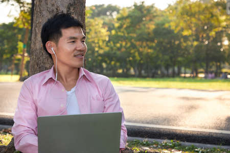 Asian man leaned against a tree while listening to soothing music from his laptop.
