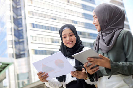 Two young Asian Muslim businesswomen stand together in a central business district.