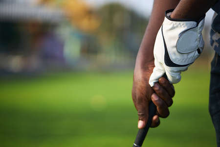 Golfer's hand holds the golf club in preparation for the hit.