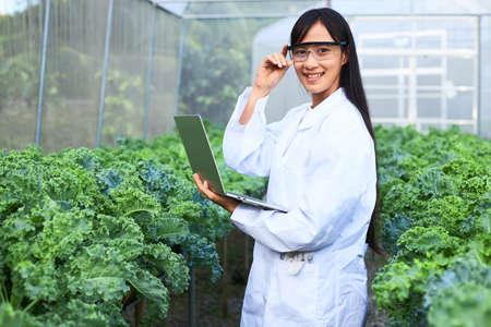 The female botanist, geneticist, or scientist is working in a nursery full of plants. Stock fotó