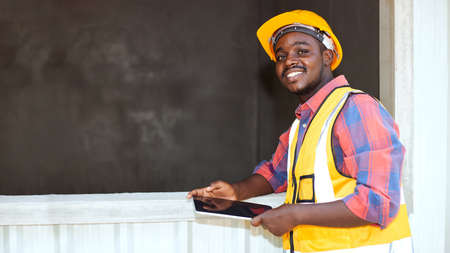 Black laborers wearing protective clothing and yellow helmets, holding the tablet, and smiling happily inside the construction site.