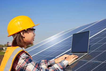A female electrical engineer is using a laptop to control the operation of the solar panel outdoors. Solar Power Management and Alternative Energy, Clean Energy.