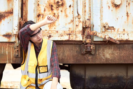 A female construction worker in a yellow vest is tired from work, here sitting next to a container. A woman worker is bored of working in hot and sunny weather.