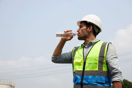 A handsome engineer or male construction worker in protective clothing and a helmet, is drinking water to quench his thirst in the harsh sunlight.