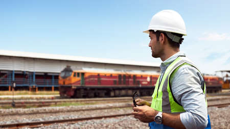 Successful Rail logistics specialists or train engineers wearing helmets and safety vests standing outdoors on the train tracks to check the readiness of work.