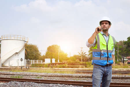 A handsome caucasian Railway engineer or Rail transport technician, wearing a reflective vest and helmet, stands and holding a walkie-talkie on an outdoor train track.