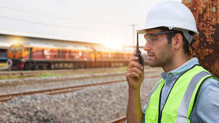 Successful Rail logistics specialists or train engineers wearing helmets and safety vests standing outdoors at the train track holds a walkie-talkie checking the readiness of work.