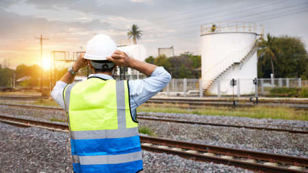 The back of a caucasian Railway engineer or Rail transport technician, wearing a reflective vest and helmet, standing outdoors in the morning when the sun is rising.