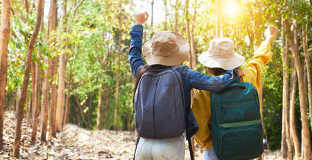 The Rear View of two Asian women carrying a backpack and wearing casual clothes is happily wandering through the national park. Female travelers spend their vacations going hiking.