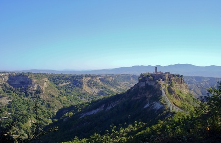 The Italian hill town of Civita di Bagnoregio rests quietly on a hilltop created by earthquake and erosion  photo