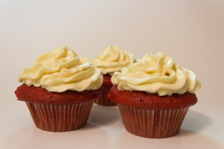 Red velvet cupcakes with buttercream icing isolated on white.