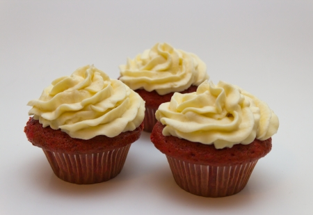 Red velvet cupcakes with buttercream icing isolated on white. photo