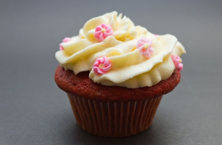 red velvet cupcake: Red velvet cupcake with buttercream icing and flower decoations isolated on black.