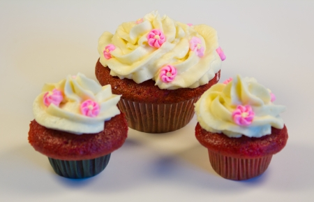 Red velvet cupcakes with buttercream icing with flower decorations isolated on white. photo