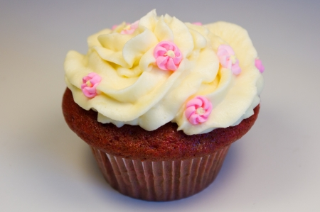 Red velvet cupcake with buttercream icing with flower decorations isolated on white. photo