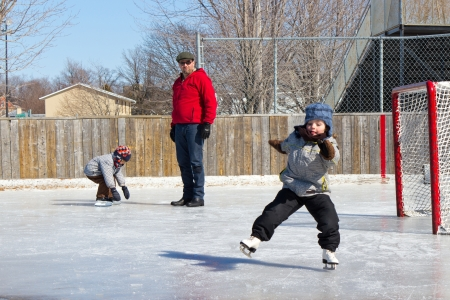 Father with son and daughter playing at the skating rink in winter  photo