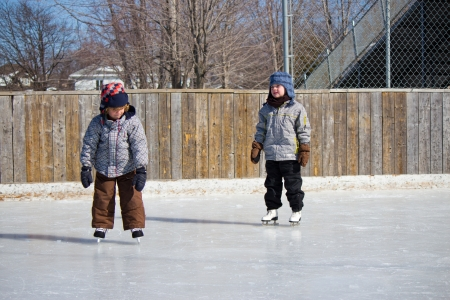 Children playing and skating at the outdoor skating rink during winter  photo