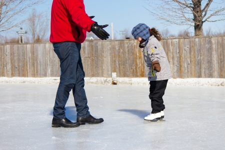 Father teaching daughter how to ice skate at an outdoor skating rink in winter  Stock Photo - 13899416