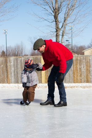 Father teaching son how to ice skate at an outdoor skating rink in winter  photo