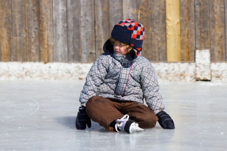 Boy learning to ice skate at an outdoor skating rink in winter. photo