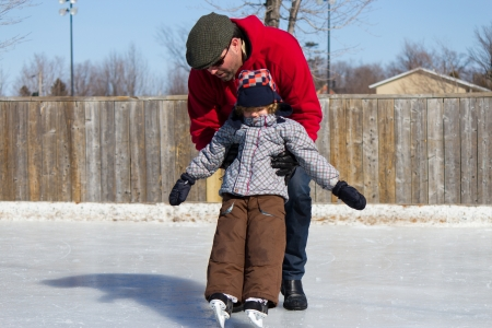 Father teaching son how to ice skate at an outdoor skating rink in winter.